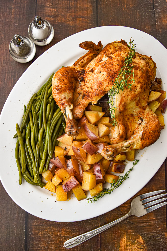overhead shot of instant pot whole chicken one pot meal with green beans and red potatoes on a white platter next to salt and pepper shakers on a brown wood background