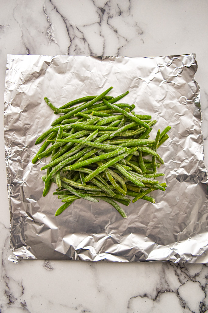 frozen green beans on tin foil on a white marble background