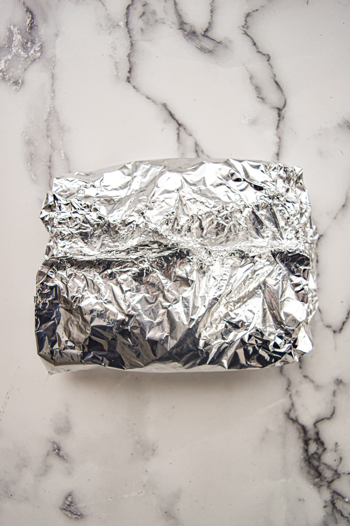 sealed foil packet holding the frozen green beans on a white marble background