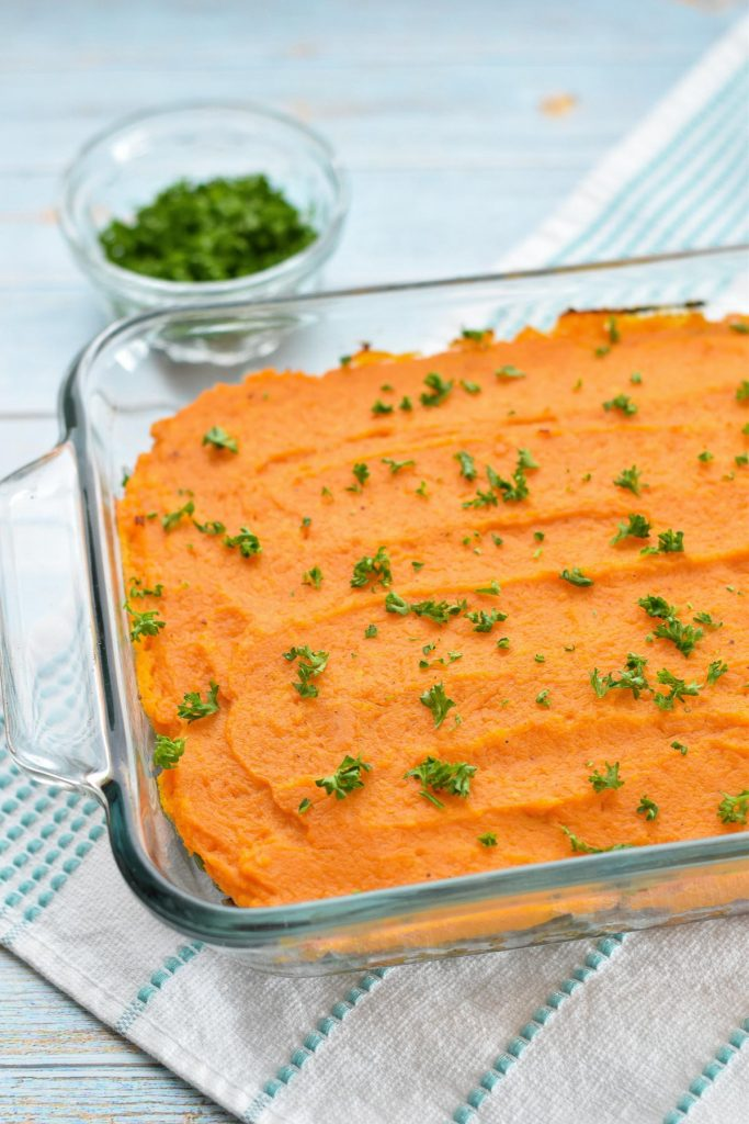 sweet potato shepherd's pie in a clear baking dish on a striped towel next to a bowl of parsley