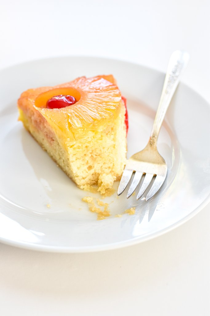 a partially eaten piece of pineapple upside down cake on a plate with a fork
