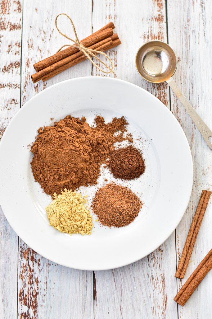 a plate of pumpkin pie spice ingredients next to cinnamon sticks and a tablespoon