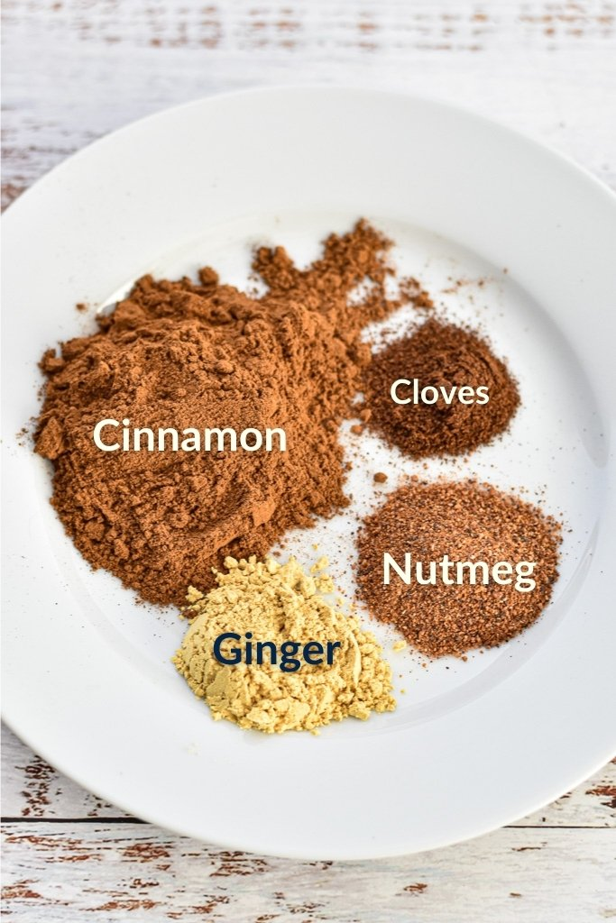 a plate illustrating homemade pumpkin pie spice ingredients: cinnamon, cloves, ginger and nutmeg