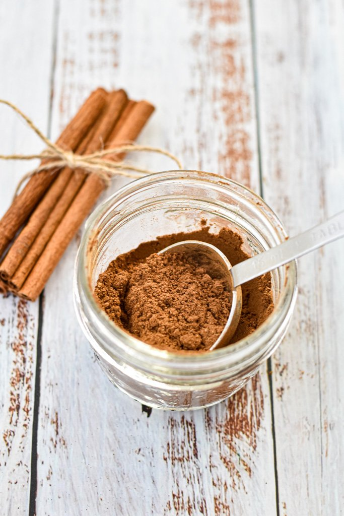 a jar of homemade pumpkin pie spice in front of a bunch of cinnamon sticks