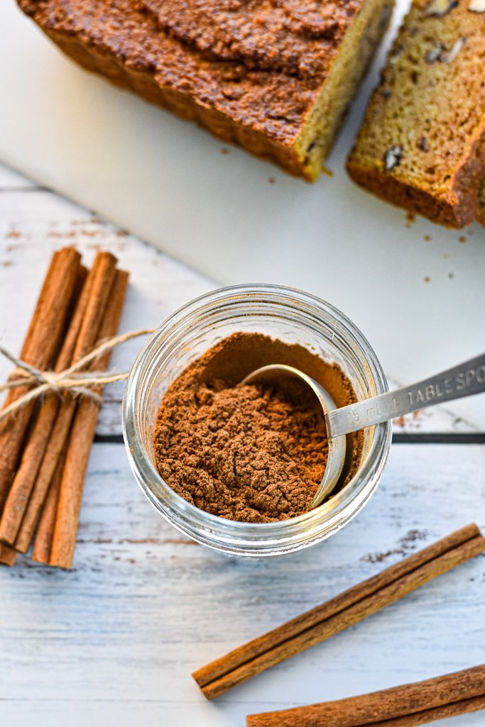 homemade pumpkin pie spice in front of sliced pumpkin bread and next to cinnamon sticks