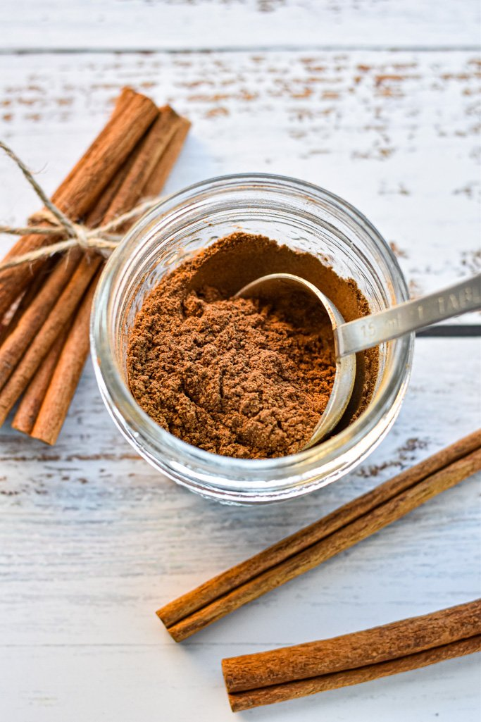 a spoon scooping a tablespoon of homemade pumpkin pie spice out of a jar that's next to cinnamon sticks