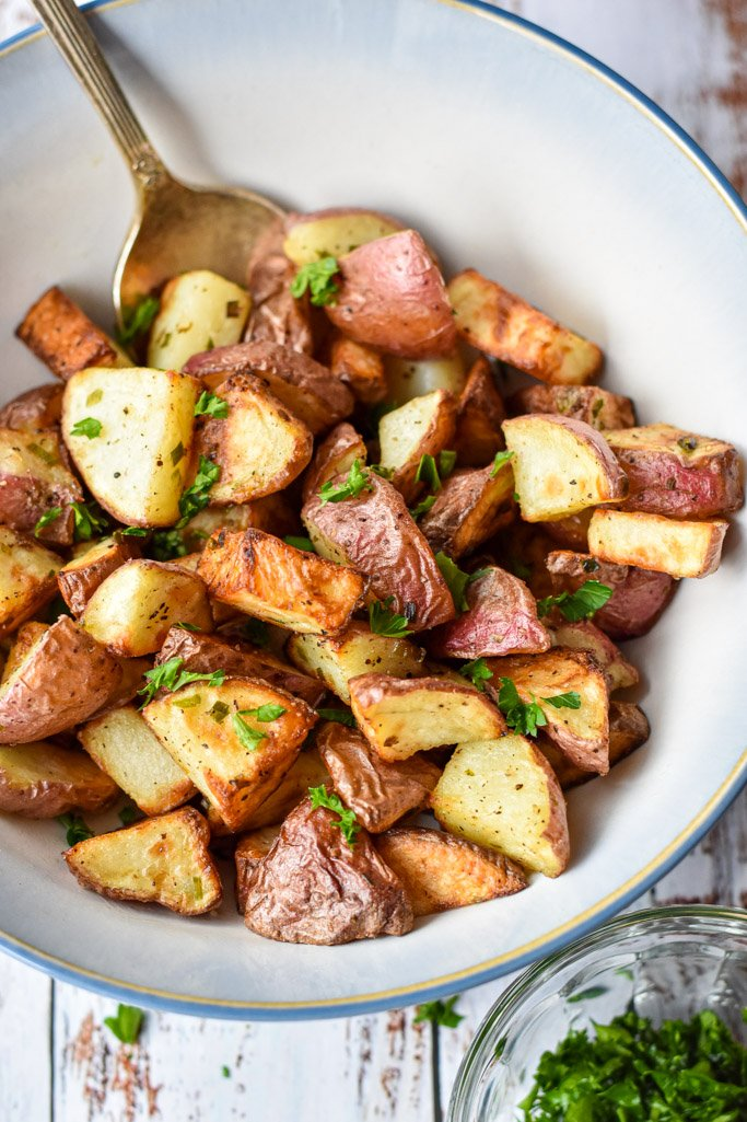 a close up of air fryer red potatoes in a bowl with a spoon