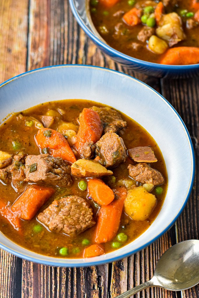 bowls of instant pot slow cooker beef stew containing meat, carrots, potatoes and peas with a spoon