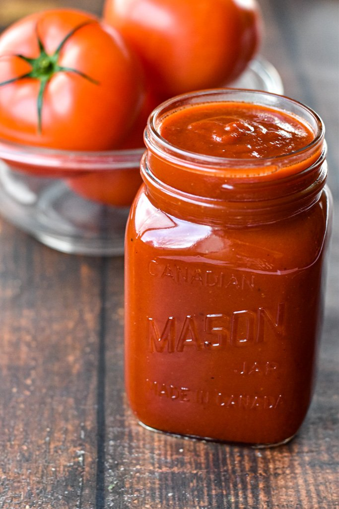 homemade ketchup in a glass jar in front of a bowl of tomatoes