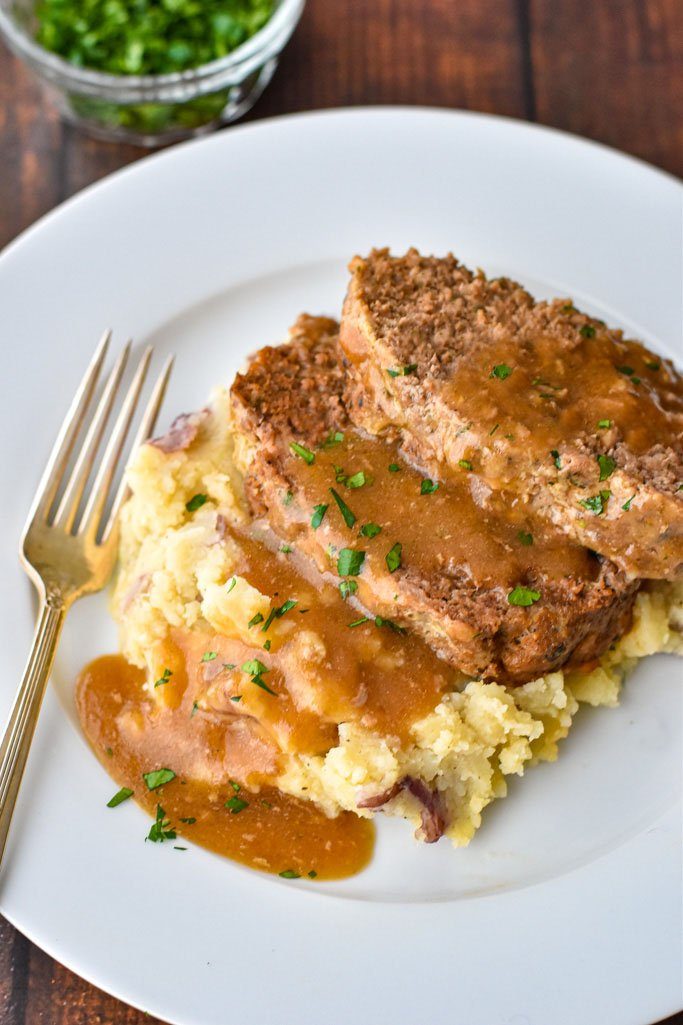 two slices of instant pot meatloaf resting on top of mashed potatoes topped with gravy on a white plate with a fork