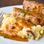 two slices of instant pot meatloaf on top of mashed potatoes and topped with gravy