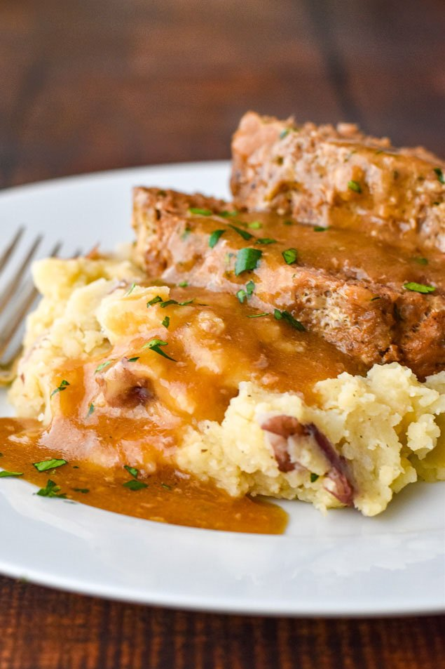 instant pot meatloaf stacked on top of mashed potatoes and covered in gravy on a white plate