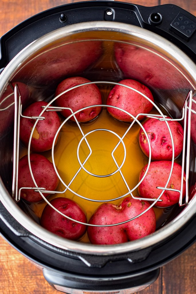overhead view of the instant pot, with beef broth and red potatoes in the bottom of the inner pot with the trivet resting evenly on top of the potatoes
