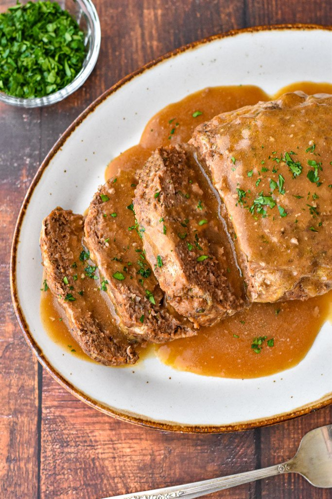 overhead shot of instant pot meatloaf on a brown rimmed platter covered in gravy and garnished with parsley
