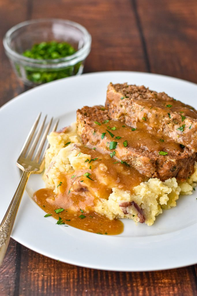 slices of instant pot meatloaf on mashed potatoes covered in gravy on a white plate with a fork, with a bowl of chopped parsley behind