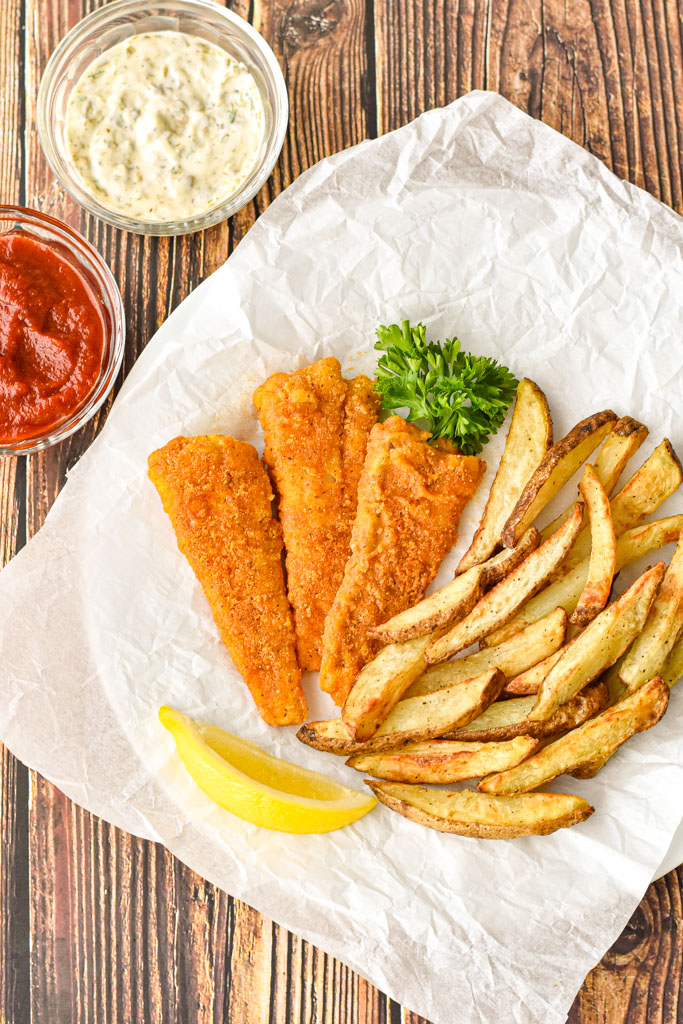 overhead shot of gluten-free fish and chips on a parchment paper covered plate with lemon and parsley next to bowls of ketchup and tartar sauce