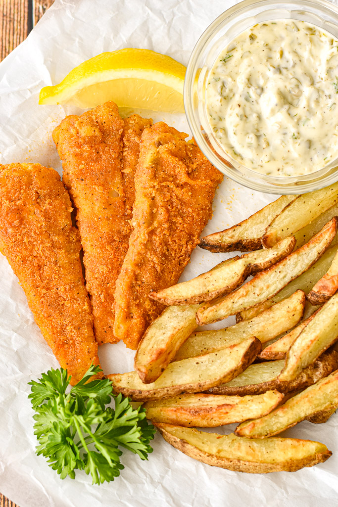 close up shot of air fryer fish and chips on white parchment paper with a bowl of tartar sauce, a slice of lemon, and a sprig of parsley