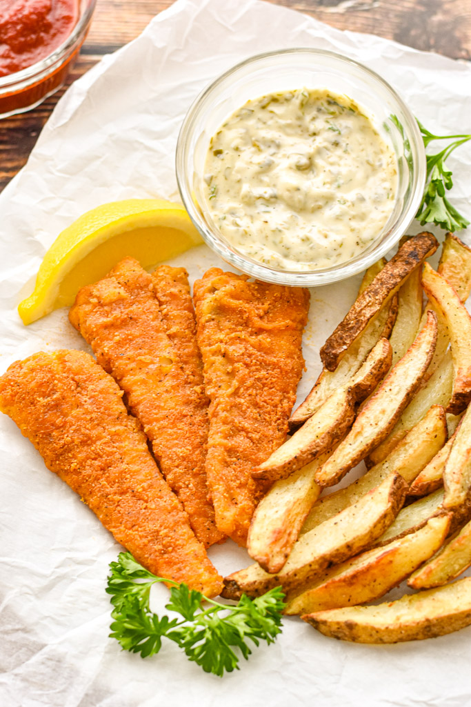 three pieces of gluten-free fish with fries on a plate with homemade tartar sauce, parsley springs, and a lemon slice