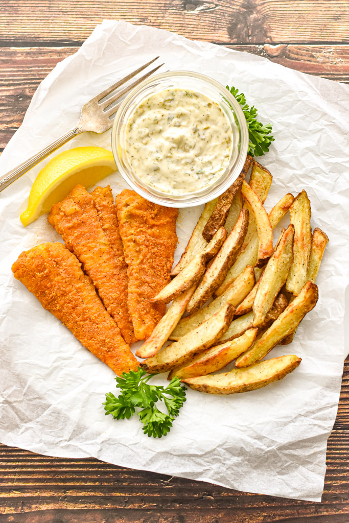 fish and chips made with the air fryer on a plate covered in parchment paper with a bowl of tartar sauce, slice of lemon, sprigs of parsley, and a fork