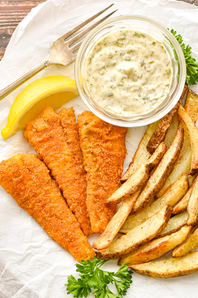 close up shot of low fodmap fish and chips, garnished by a slice of lemon and parsley springs on white parchment paper with a fork
