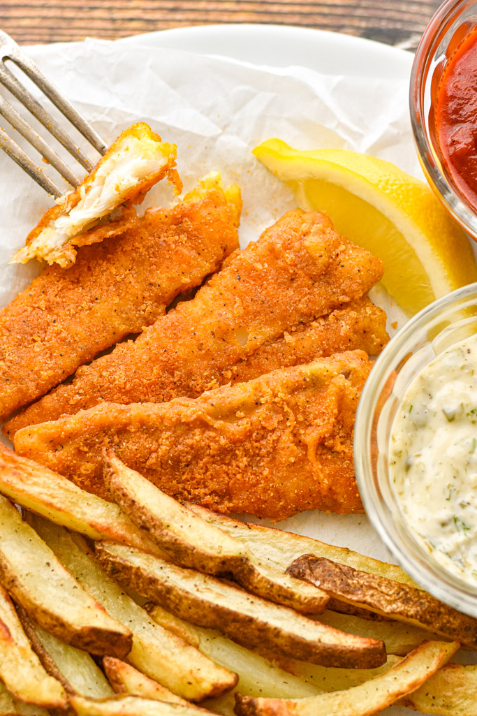 air fryer fish and chips on parchment paper next to bowls of homemade tartar sauce and ketchup and a slice of lemon